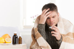 Portrait of sick middle aged man with thermometer. Stock Image