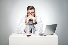 Portrait of sick scribble young boss in white shirt, scarf and black tie are sitting in office and need to finish important report. Have grippe virus. Studio stock photos