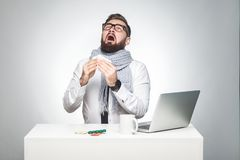 Portrait of sick scribble young boss in white shirt, scarf and black tie are sitting in office and need to finish important report. Have grippe virus. Studio royalty free stock photography