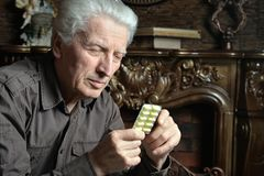 Portrait of sick senior man with pills Stock Photo