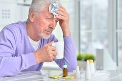 Portrait of sick senior man with pills posing. At home royalty free stock image