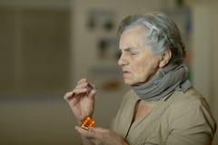 Senior woman taking pills. Portrait of sick senior woman taking pills stock photo