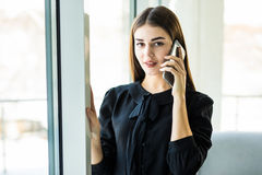 Portrait from side pretty businesswoman in black dress in cafeteria. She is speaking on phone. Stock Image