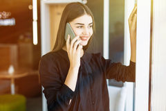 Portrait from side pretty businesswoman in black dress in cafeteria. She is speaking on phone, looking in window Royalty Free Stock Photo
