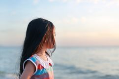 Portrait side view little child girl standing on beach at sunset light with looking at sea royalty free stock images