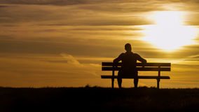 Portrait of a silhouette man sitting on a bench looking towards the sunset, with copy space Royalty Free Stock Photos