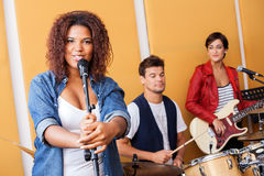 Portrait Of Singer Performing With Band In. Portrait of female singer performing with band members in recording studio Royalty Free Stock Photos