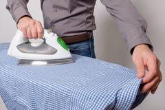 Portrait of single man ironing a shirt Royalty Free Stock Photos