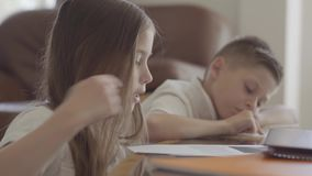 Close up portrait of twin sister and her tired brother twin leafing through notebooks with homework exhausted after stock footage