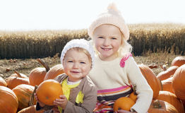 Portrait of sisters with pumpkin sitting on farm Royalty Free Stock Image