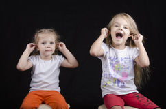 Portrait of the sisters, and two little girls, have joined hands behind the ears. Portrait of the sisters - two little girls on the chairs. Girls fun smiling and Stock Photography