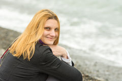 Portrait of sitting on beach smiling young woman in cold weather Royalty Free Stock Photos