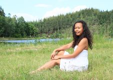 Portrait of sitting pretty girl. Portrait of pretty Papuan girl in white dress - smiling young Indonesian woman sitting in grass in front of Rimov Dam with Stock Photos