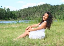 Portrait of sitting pretty girl. Portrait of pretty Papuan girl in white dress - smiling young Indonesian woman sitting in grass in front of Rimov Dam with Royalty Free Stock Images