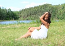 Portrait of sitting pretty girl. Portrait of pretty Papuan girl in white dress - smiling young Indonesian woman sitting in grass in front of Rimov Dam with Royalty Free Stock Photo