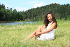 Portrait of sitting pretty girl. Portrait of pretty Papuan girl in white dress - smiling young Indonesian woman sitting in grass in front of Rimov Dam with Royalty Free Stock Image