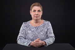 Portrait of sitting senior woman looking at camera stock photography