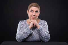 Portrait of sitting thinking senior woman Royalty Free Stock Images