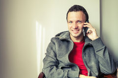 Portrait of sitting young man talking on mobile phone Royalty Free Stock Photography