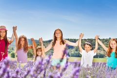 Happy kids holding hands up in lavender field Stock Image