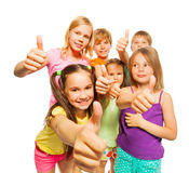 Portrait of six kids showing thumbs up. Image of six kids with thumbs up standing close to each other on a white background Stock Image