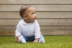 Portrait of a six months old baby girl sitting on the grass on a stock images