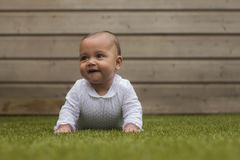 Portrait of a six months old cute baby girl smiling and lying on royalty free stock images