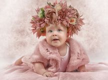 Portrait of a six months old little girl. Portrait of a sweet little girl six months old with a wreath of flowers on her head in pink stock photography
