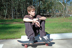 Portrait of a Skater. A teenaged boy rests with his skateboard at a suburban park Royalty Free Stock Photos