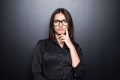 Closeup portrait, skeptical, serious senior young woman looking suspicious, disapproval on face isolated black background. Portrait, skeptical, serious senior Stock Images