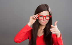 Portrait of a skeptical woman. Skeptical woman in red-framed glasses pointing at camera, studio shot, gray background royalty free stock photos