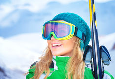 Portrait of skier girl. Closeup portrait of cute smiling skier girl wearing sportive goggles and holding in hands ski, active winter vacation, happiness and royalty free stock image