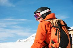 Portrait of a skier in an orange overall with a backpack on his back in a helmet stands against the background of a. Beautiful Caucasian mountain landscape with Stock Image