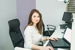 Portrait of skilled administrative manager working on laptop com. Puter in office satisfied with occupation, young female receptionist organizing working Stock Photos