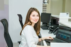 Portrait of skilled administrative manager working on laptop computer in office satisfied with occupation, young female receptioni. St organizing working Royalty Free Stock Images