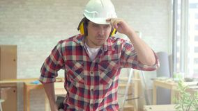 Portrait of a skilled professional man with a drill in his hands and a helmet. In a modern workshop stock video