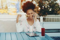 Sexy black lady with smartphone in cafe outdoor Royalty Free Stock Photo