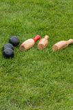 Portrait of skittles lying on lawn. Set of fallen traditional wooden skittles outdoors on grass with black balls in summer in UK Royalty Free Stock Photos