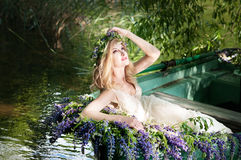 Portrait of slavic or baltic woman with wreath sitting in boat with flowers. Summer Royalty Free Stock Photography