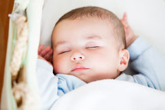 Portrait of a sleeping baby lying in his cradle Stock Images