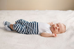 Adorable funny white Caucasian baby with blue grey eyes lying on bed