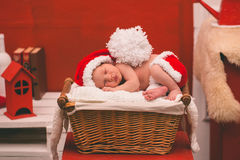 Portrait of sleeping newborn baby boy in Santa clothes. Royalty Free Stock Images