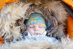Portrait of sleeping newborn baby in warm winter clothes Stock Photos
