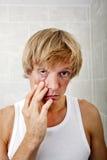 Portrait of sleepy man pulling eyelid in bathroom Stock Images