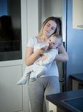 Portrait of sleepy mother feeding baby son from bottle on kitche Stock Images