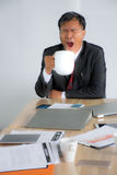 Portrait of a sleepy tired Asia businessman snoozing and having a coffee at the work place/Isolate Stock Images