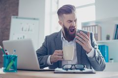 Portrait of a sleepy tired businessman snoozing and having a coffee at the work place royalty free stock photography