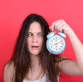 Portrait of sleepy young female in chaos holding clock against r Stock Image