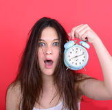 Portrait of sleepy young female in chaos holding clock against r royalty free stock image