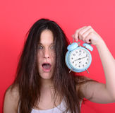 Portrait of sleepy young female in chaos holding clock against r Stock Photo